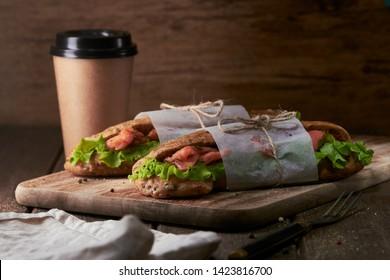 Tasty salmon sandwich with coffee