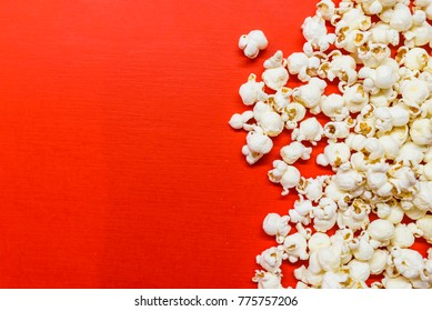 Tasty salted popcorn isolated on red background. Popcorn border isolated on red, clipping path included. Cinema, movies and entertainment concept.