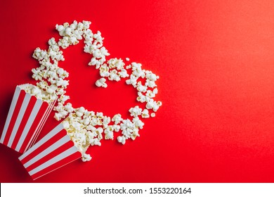Tasty salted popcorn in striped cardboard box on red background. Top view. Flat lay. Copy space. Heart shape, Valentines day