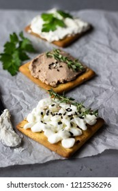 Tasty salted square crackers with cream cheese, cottage cheese, liver pate, seeds and herbs on parchment paper.