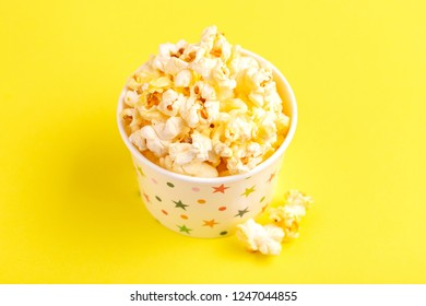 Tasty salty popcorn in paper cup on bright yellow backgraund. Pastime watching movies. Cinema snacks. Copy space