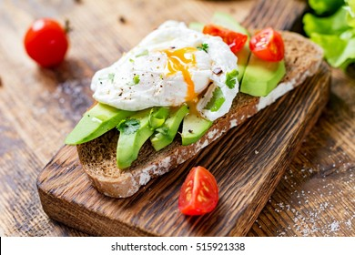 Tasty sandwich with avocado, tomato and poached egg on wooden chopping board, close up, selective focus. Healthy delicious breakfast or lunch