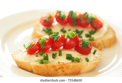 Tasty sandwich with cream cheese, baby tomatoes and spring onions on white loaf bread