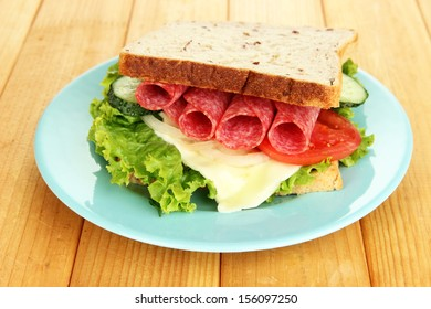 Tasty sandwich with salami sausage and vegetables on blue plate, on wooden background
