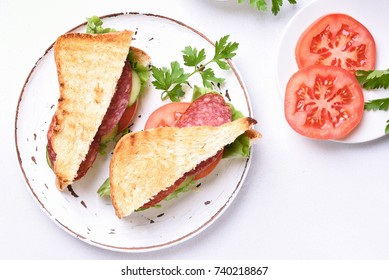 Tasty sandwiches with salami, tomatoes, cucumber and lettuce on white stone background. Top view.