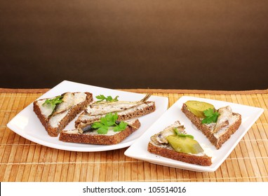 Tasty sandwiches with sprats on plate on wooden mat on brown background