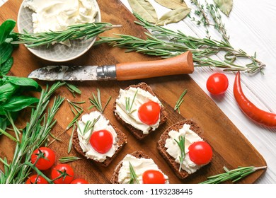 Tasty sandwiches with spread, tomatoes and herbs on wooden board, top view