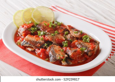 Tasty sardines in tomato sauce with lime and parsley close-up on a plate. Horizontal