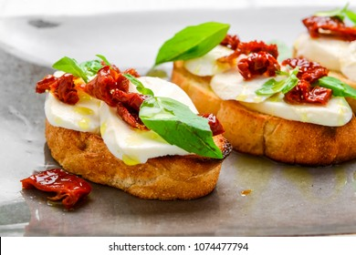 Tasty savory Italian appetizers, or bruschetta, on slices of toasted baguette garnished with basil, close up on a wooden board