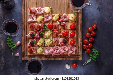 Tasty savory tomato Italian appetizers, or bruschetta, slices of toasted baguette topped with ham, prosciutto on a wooden board