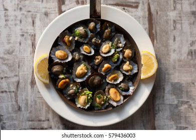 tasty seafood - grilled limpets served with lemon. Lapas grelhadas. Madeira's traditional dish and a typical snack of the Canary Islands. Grilled Limpets in Madeira Islands.