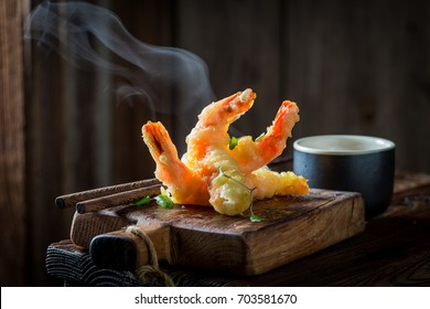 Tasty shrimp in tempura with red sauce on black background