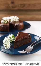 Tasty Siberian dessert. Bird cherry cake with chocolate ganache served with white flowers of bird cherry on dark blue plate on white background copyspace