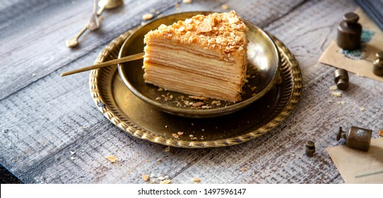 tasty slice of homemade creamy layered traditional russian cake napoleon on vintage gold metal plates on grey wooden table