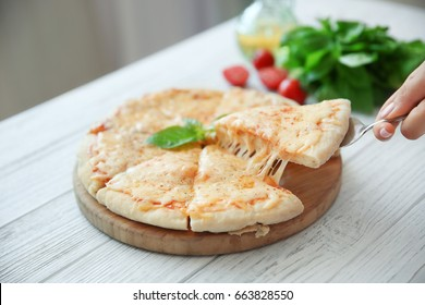 Tasty sliced pizza with basil leaves on wooden table
