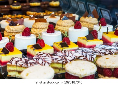 Tasty small cakes are laid out on a show-window in cafe