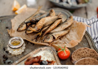 Tasty smoke-dried horse mackerel fish on the paper with a sun dried and fresh tomatoes, oil and bread on the metal tray.