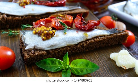 Tasty smorrebrod on a wooden board. Sandwiches with black rye bread, sun-dried tomatoes, salted anchovies, mustard.