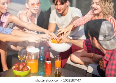 Tasty snack. Cheerful friends eating potato chips and enjoying time together outdoors