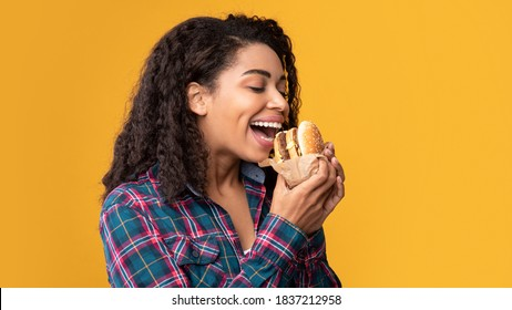 Tasty Snack. Closeup Portrait Of Hungry Black Female Model Eating Hamburger. African American Woman Holding And Biting Tasty Fast Food, Isolated Over Orange Studio Background, Banner, Copy Space