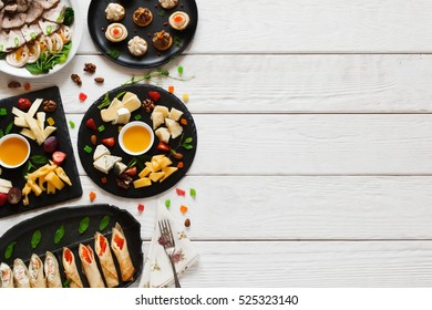 Tasty snacks on white wooden table, free space. Variety of light appetizing luxury gourmet meals in right side of picture with copy space for text