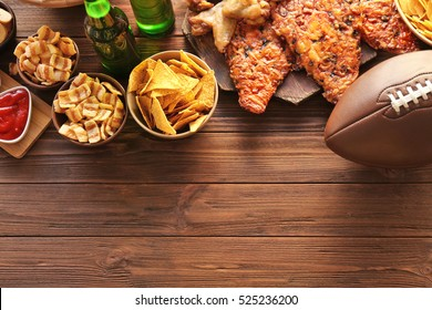 Tasty snacks and rugby ball on wooden table