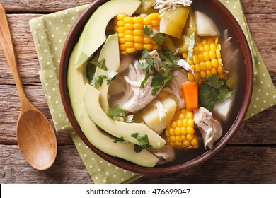Tasty soup ajiaco with chicken and vegetables close up in a bowl on the table. horizontal view from above