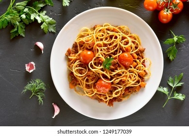 Tasty spaghetti with minced meat and cherry tomatoes on black stone background. Top view, flat lay