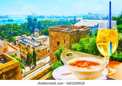 The tasty Spanish rice pudding (arroz con leche) and a glass of sparkling cava sangria in outdoor restaurant with top view on city and port of Malaga, Spain