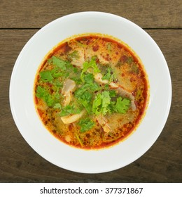 The tasty spicy pork tom yum soup (hot and sour soup) in white ceramic bowl, homemade Thai food.