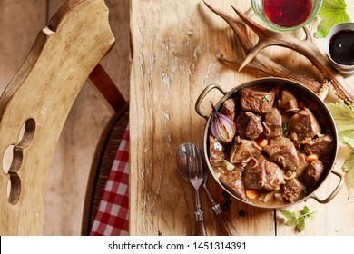 Tasty spicy wild venison goulash or ragout with vegetables and fresh herbs served in a copp pot on a rustic table set with wine, coffee and deer antlers viewed top down