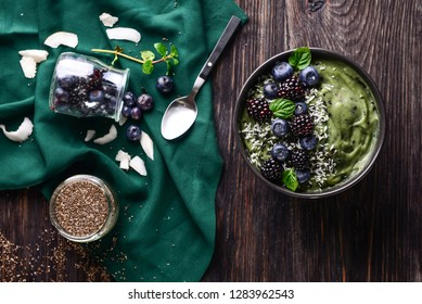 Tasty spirulina smoothie with berries in bowl on dark wooden table