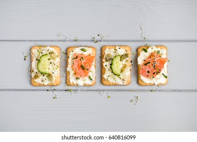 Tasty square crackers with cream cheese, cucumbers, salmon, pumpkin seeds and micro greens. Appetizers on grey table. Healthy vegetarian snacks, top view, flat lay