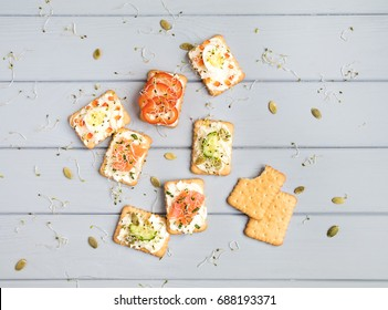 Tasty square crackers with cream cheese, sweet pepper, salmon, eggs, cucumbers, pumpkin seeds and micro greens. Appetizers on grey table. Healthy snacks, top view, flat lay