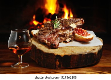 tasty steak on a background of a cozy fireplace and a glass of cognac