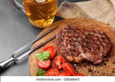 Tasty steak with tomatoes and beer on cutting board