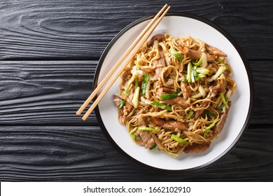 Tasty stir-fried Chinese egg noodles with napa cabbage green onions and pork closeup in a plate on the table Horizontal top view from above