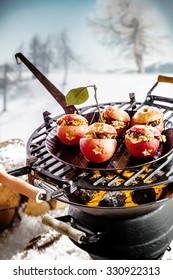 Tasty stuffed apples with nuts and raisins roasting on a grill over hot coals on a winter barbecue outdoors in a snowy landscape ready for a winter BBQ party and Christmas celebration