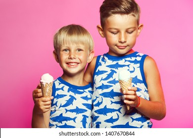 Tasty summer obsession concept. Happy young handsome hipster boys wearing sleeveless shirts with sharks, hugging, eating melting ice cream in waffle cone over pink colour background. Studio shot