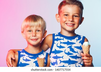 Tasty summer obsession concept. Happy young handsome hipster boys wearing sleeveless shirts with sharks, hugging, eating melting ice cream in waffle cone over pink & blue background. Studio shot