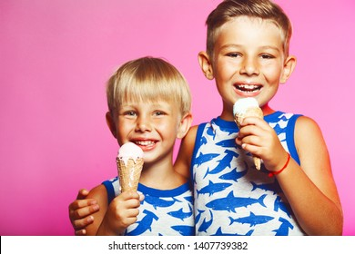 Tasty summer obsession concept. Happy young handsome hipster boys wearing sleeveless shirts with sharks, hugging, eating melting ice cream in waffle cone over pink colour background. Copy-space