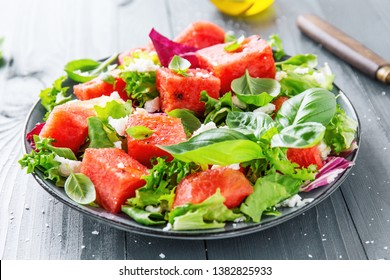 Tasty summer refreshing watermelon salad with salad leaves, basil, feta and olive oil. Served on plate on grey table. Closeup