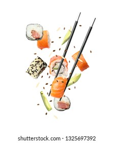 Tasty sushi rolls, avocado and chopsticks on white background