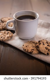 Tasty sweet breakfast with a cup of coffee and chocolate cookies on beige doily on dark wood table