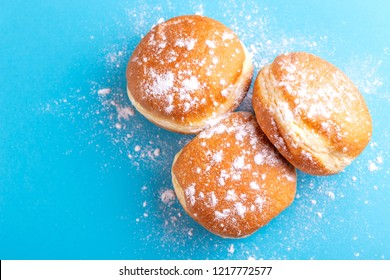 Tasty sweet donuts with powdered sugar on bright blue background. Traditional Jewish sweet Hanukkah dish