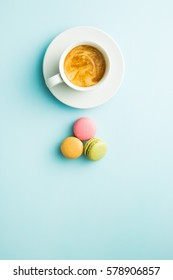 Tasty sweet macarons and coffee cup. Macaroons on blue background. Top view.