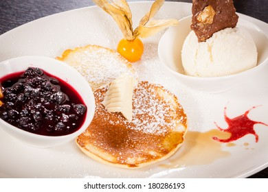 tasty sweet pancakes with vanilla icecream fruit jam and syrup topping