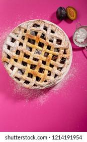 Tasty sweet plum pie on pink background
