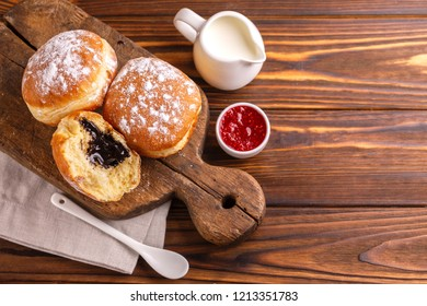 Tasty sweet sugary chocolate donuts with raspberry jam and milk on old wooden rustic cutting board. Traditional Jewish sweet Hanukkah dish. Wooden background