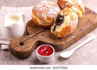 Tasty sweet sugary chocolate donuts with raspberry jam and milk on old wooden rustic cutting board. Traditional Jewish sweet Hanukkah dish. Gray marble background